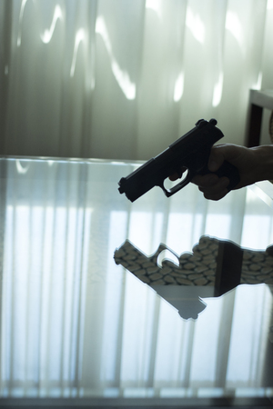 Automatic pistol gun on glass table in bedroom