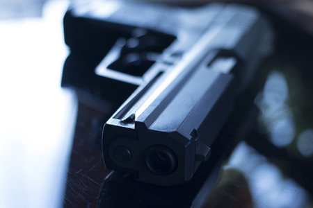 Automatic pistol handgun in artistic light effect moody atmospheric photo creative artistic closeup