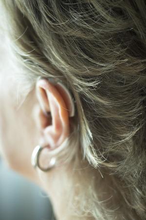 Deaf lady with modern technology digital hearing aid in her ear.
