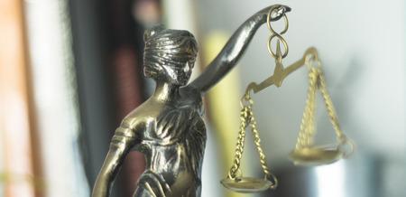Brązowy posąg bogini Temidy z wagą sprawiedliwości w kancelarii adwokackiej. Zdjęcie Seryjne