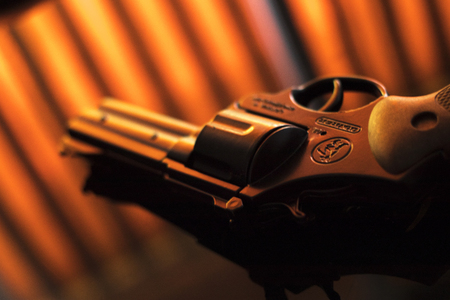Pistol automatic handgun weapon on table in hotel bedroom in atmospheric dark dramatic photo. Stock Photo