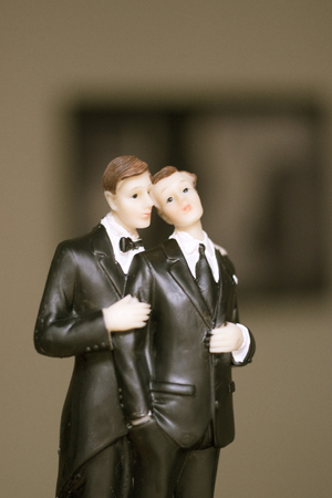Cake topper gay wedding couple of two male grooms holding romantic marriage embrace of LGBT love. Stock Photo