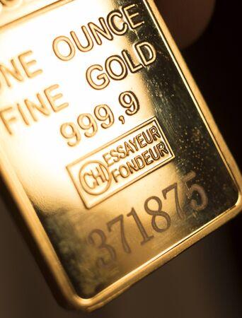 Feines massives Gold 999,9 eine Unze Goldbarrenbarren-Edelmetallbarren-Nahaufnahme isoliertes Foto.