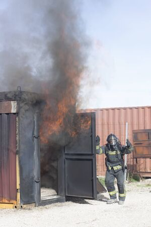 Firefighter putting out fire training station extinguisher backdraft emergency safety drill with ship container.