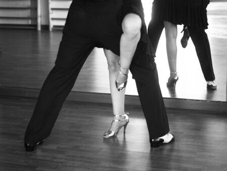 Ballroom dance salsa dancer instructors man and woman couple dancing in shcool rehearsal room