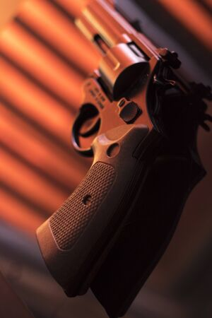 Pistol automatic handgun weapon on table in hotel bedroom in atmospheric dark dramatic photo. 写真素材