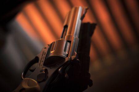 Pistol automatic handgun weapon on table in hotel bedroom in atmospheric dark dramatic photo. Imagens