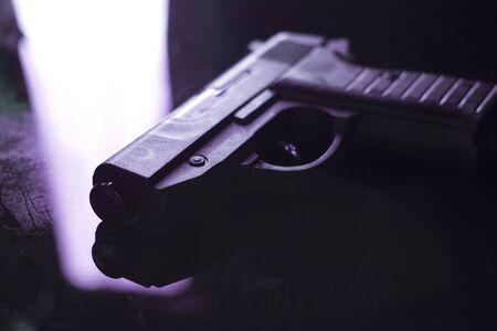 Automatic pistol handgun in artistic light effect moody atmospheric photo creative artistic closeup