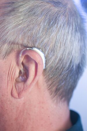 Caucasian white old aged man wearing modern digital hearing aid in ear with grey hair.