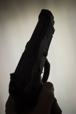 Pistol automatic handgun weapon in silhouette in hand of killer atmospheric dark dramatic photo. Banco de Imagens