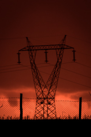 Apocalypse cloudscape suggesting a horror scene. Fiery red landscape with backlit power pylon.