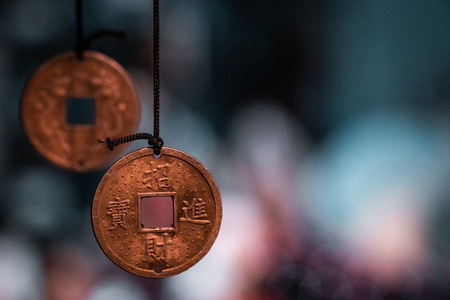 Orinetal, magical pendants. Traditional asiatic and chinese currency, transformed into fortune coins with handmade engravings. Bronze, copper, gold necklace, black thread, blurry blue background.