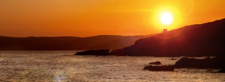 Sunset panorama over waves and sea, cliffs, silhouttes, people, fishermen  Stock Photo