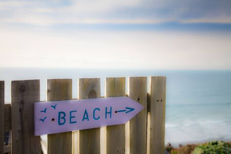 Beach direction sign - wooden and painted pink, on slated fence, backlit with dreamy atmosphere, waves and sky blurred in background. photo