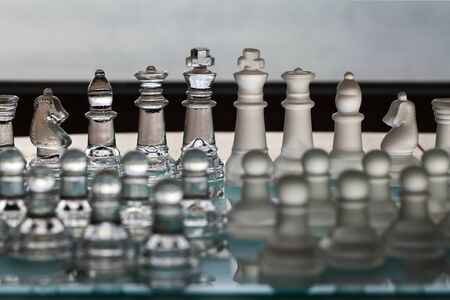 amalgamate: Chess Set as a business concept series with themes of strategy, competetion, mergers, CEO, management, companies, politics, survival and winning. Main pieces in focus, and lowly pawns in foreground blurred.