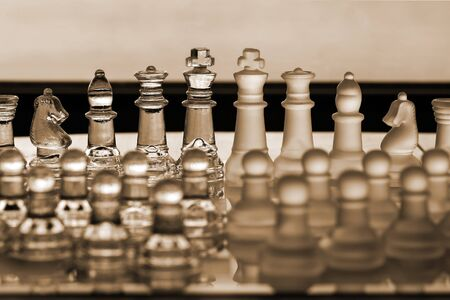 Chess Set as a business concept series with themes of strategy, competetion, mergers, CEO, management, companies, politics, survival and winning. Main pieces in focus, and lowly pawns in foreground blurred. photo