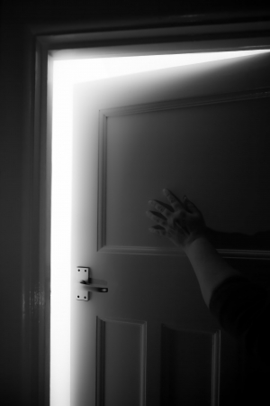 A female hand ready to push open a door with light behind, with themes of domestic abuse, fear, mystical doors or confronting the unknown  facing fears. Stock Photo