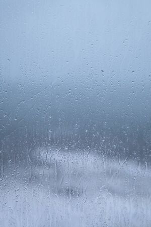 smeary: Raindrops on a windowpane, smeary, blurry, and wet, the stormy sea and cloudy sky in background, with themes of staying indoors on a wet day  holiday  weekend.