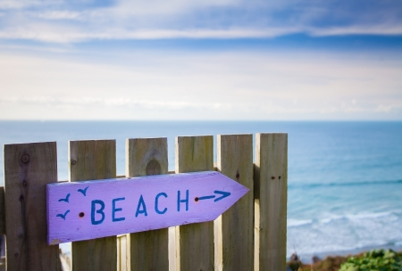 colloquial: Beach sign path marker - pink and blue in Summer - with sea and sky in background