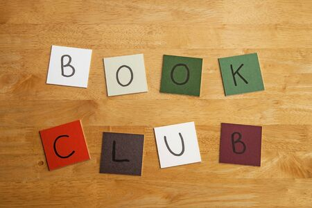 arty: BOOK CLUB in letters on square color tiles - wooden background