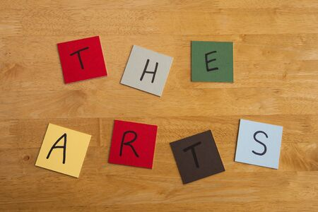 arty: The Arts in capital letters and words, arty design on square color tiles on wooden background - series