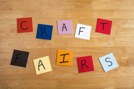 Craft Fair in letters  words on colored square tiles for arts and crafts fairs on wooden background. photo