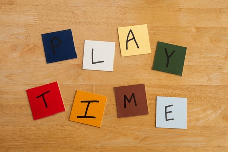 PLAY TIME written in letters on square tiles on wooden background - for education / schools / teachers! Stock Photo - 17453458