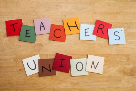 Teachers Union written on square color tiles in capital letters with wooden background.