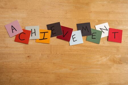 ACHIEVEMENT in letters on square tiles - education, schools or business. Stock Photo - 17453471