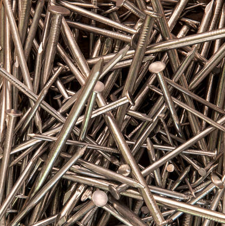 galvanised: Variety of nails in a pile as jumbled pattern and background texture design.