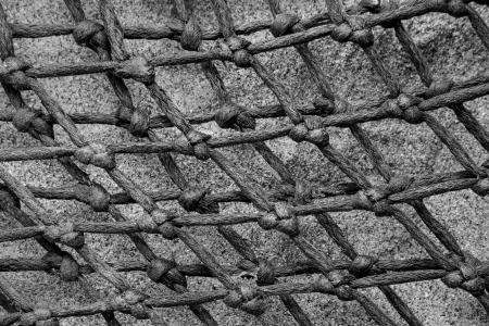 lobster pot: Diamond patterns of net abstract, with rope and knots tied from a lobster pot, natural sand in background.
