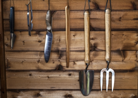 Rack of garden tools in a wooden shed ready for gardening  Stock Photo
