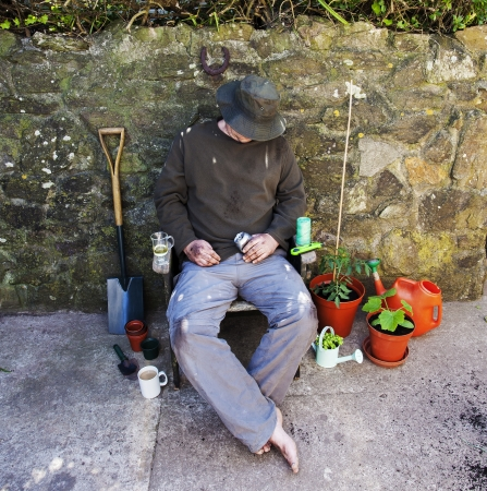 Male gardener, bare feet, grubby and asleep in garden chair amongst his tools after gardening  photo