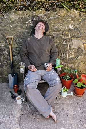 Male gardener happy and asleep in garden chair amongst his tools after gardening  photo