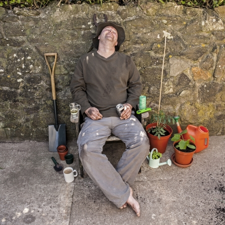 Male gardener, bare feet, grubby, happy and asleep in garden chair amongst his tools after gardening