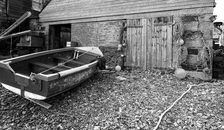 colloquial: Boat with fishermans jacket on near boat shed on shingle beach - black and white.