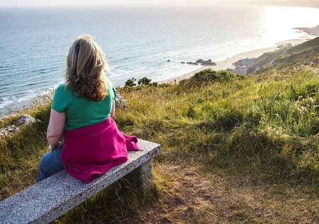 Lady Walker on Bench Resting and Gazing Out to Sea - Landscape  photo