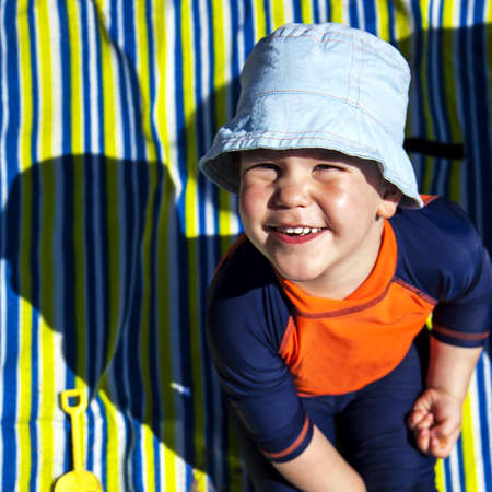 Happy young boy in hat at beach in the sunshine, on stripey beach towel  photo