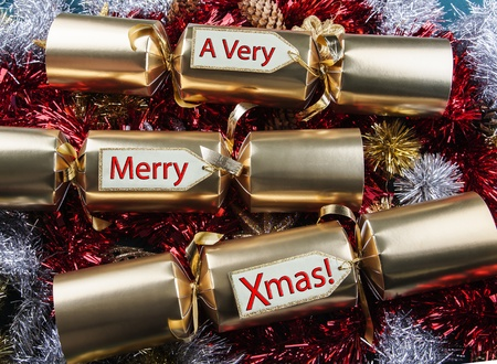christmas cracker: Merry Xmas   Christmas Crackers - with red, gold, silver tinsel  Stock Photo