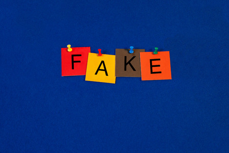 untrue: Fake - sign for unreal, copies, fakes, corruption and untruth - on noticeboard with letters and pins
