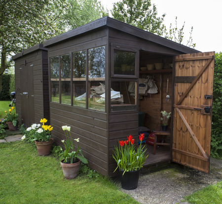 Garden shed exterior in Spring, with door open, tools, flowers, and plant pots.