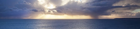 Amazing skyscape, very long and thin panorama with sunset rays behind clouds over ocean.