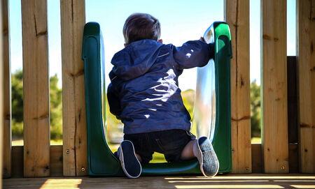bonne aventure: Enfants jouant sur parc toboggan, se demandant se il devrait faire le saut.