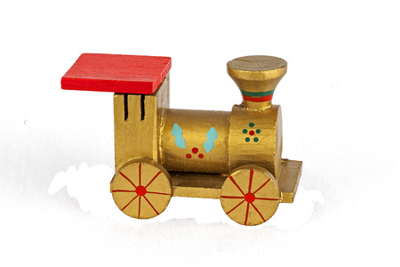 toy train: Wooden toy train Christmas decoration in gold green and red isolated on white background. Stock Photo