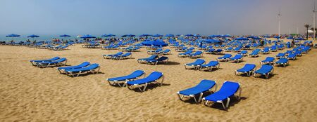 good weather: Sun loungers on beach waiting for tourists sunbathing as sea mist clears to blue skies.