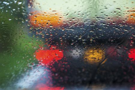 Rijden in de regen slecht weer op de wegen het verkeer komende wazig regendruppels op de voorruit in beeld in het centrum van vervaging te vegen.