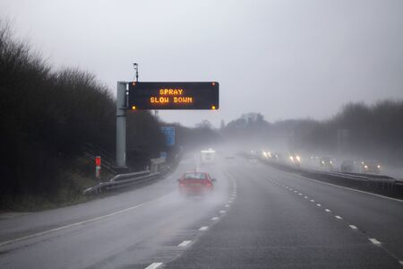 adverse: Rain on the highway  road  adverse driving conditions on the motorway  sign to slow down. Stock Photo