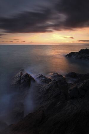 haunting: Dramatic and haunting view of sunset over the sea, in Cornwall, UK - Cornish Seascape - Long Exposure.