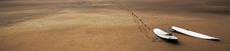 sand surfing: Surfboards, footprints and sand. Surfing beach panorama. Stock Photo