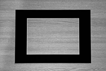 black picture frame: Empty black picture frame  mount on gray wooden background.